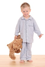 3-4 years old boy in pijama with his teddy bear isolated