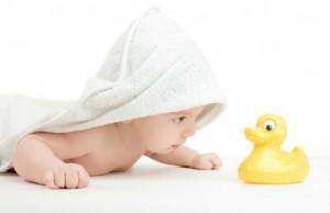 Baby mit Bademantel schaut Quitscheente an