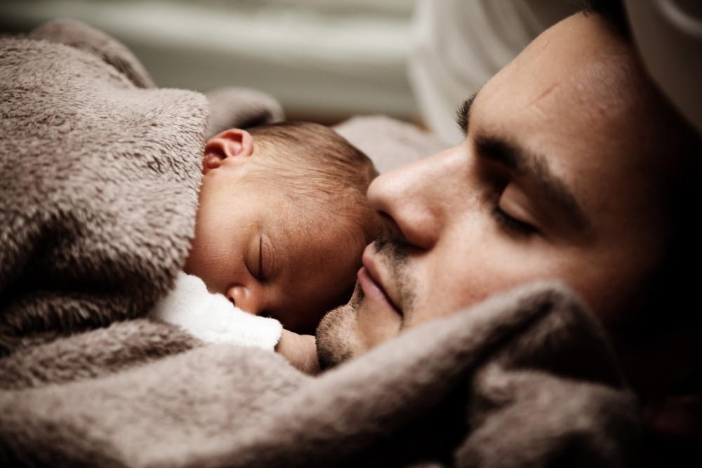 Papa schläft mit Baby auf dem Bauch