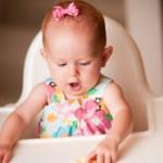 Baby mit kleiner Schleife im Haar im Hochstuhl