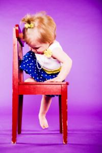 Mädchen in schickem Outfit klettert von Stuhl