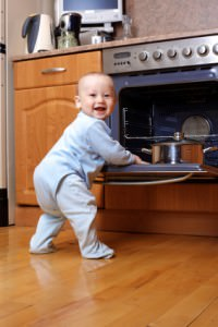 funny baby cooking at stove