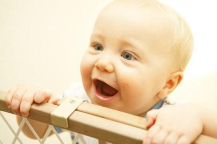 Baby lacht und schaut über Laufgitter