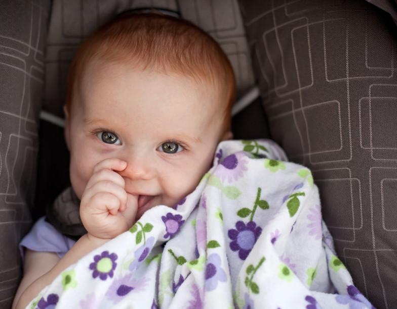 Baby mit Daumen im Autositz