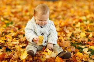 Baby spielt im Laub