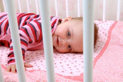 Blick durch Gitterstäbe vom Bett auf Baby in rosa-rot