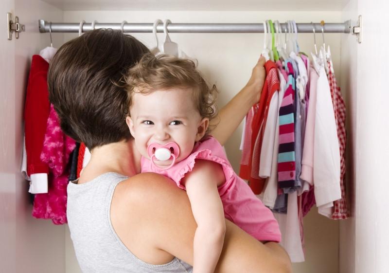 Baby auf dem Arm von Mama vor seinem Kleiderschrank_XXL
