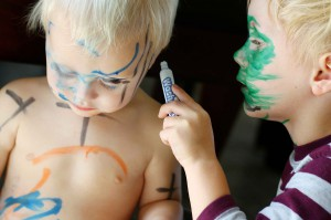Young Child Coloring Baby Brother's Face