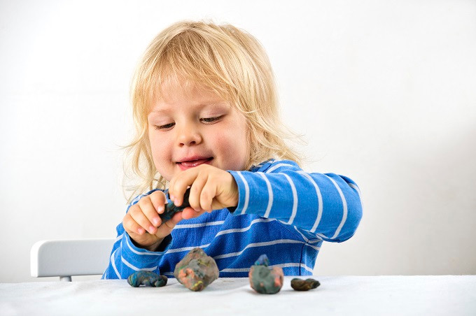 Three year old boy plays with plasticine