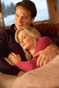 Middle Aged Couple Relaxing On Sofa In Chalet With Winter View