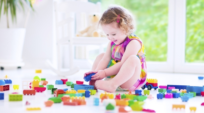 Adorable laughing toddler, cute little girl with curly hair wearing a pink summer dress, playing with colorful blocks and toys sitting on a floor in a sunny bedroom with a big window