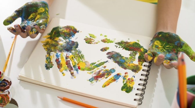 Hands of girl making multicolored hand prints